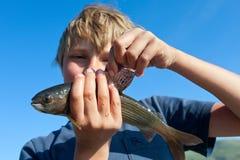 Grayling уловленный мальчиком стоковая фотография
