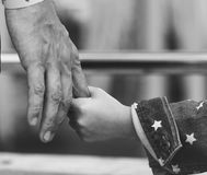 Grayscale closeup of daughter holding father`s hand Stock Photos