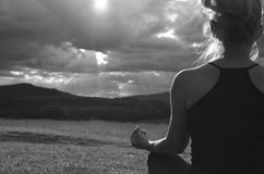 Grayscale Meditating Lady. Grayscale image of a lady who is meditating on a field faced to the sun behind stormy sky on west in late afternoon royalty free stock images