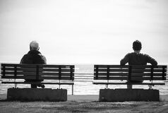 Grayscale Photo 2 Person Sitting in a Separate Benches on the Seaside Stock Image