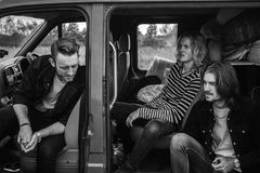 Grayscale Photo of 3 Man on Vehicle Royalty Free Stock Images