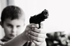 Grayscale Photo of a Boy Aiming Toy Gun Selective Focus Photography Stock Image