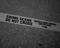Grayscale Photo of Crime Scene Do Not Cross Tape Stock Image