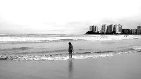 Grayscale Photo of Female Standing Seashore Stock Photo