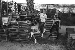 Grayscale Photo of Four Women on Wooden Pallets Stock Photo