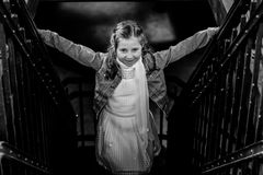 Grayscale Photo of Girl Standing on Stairs Holding Hand Rails royalty free stock image