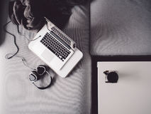 Grayscale Photo of Laptop Computer With Cooling Pad and Headphones on Sofa Royalty Free Stock Photography