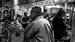 Grayscale Photo of Man in the Center of Market Stock Photography