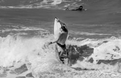 Grayscale Photo of Man Riding over Surfboard on Sea Waves stock photo