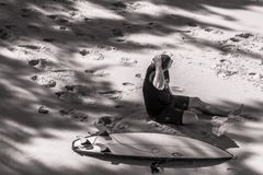 Grayscale Photo of Man Sits Beside Surfboard on Sand Royalty Free Stock Photos