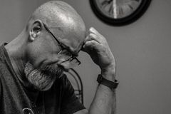 Grayscale Photo of Man Thinking in Front of Analog Wall Clock stock image