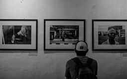 Grayscale Photo of Man Wearing White Cap in Front of Three Paintings Royalty Free Stock Images