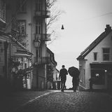 Grayscale Photo Of Man Beside Woman Under Umbrella Walking On Pavement Stock Photo