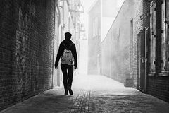 Grayscale Photo of Person Near Brick Wall Royalty Free Stock Photos