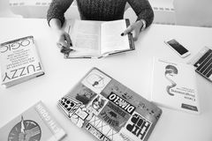 Grayscale Photo of Person Sitting Near Table With Books stock image