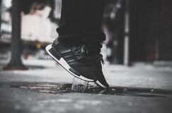 Grayscale Photo of Person Wearing Adidas Nmd Jumping on Puddle Stock Images