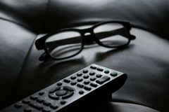 Grayscale Photo of Remote Control Near Eyeglasses Royalty Free Stock Photos