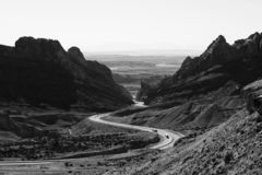 Grayscale Photo of Roadway Surrounded With Rocky Mountains royalty free stock photo