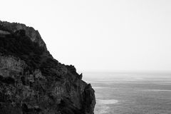 Grayscale Photo of Rocky Cliff by the Sea at Daytime Stock Photos