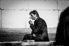 Grayscale Photo of Smoking Man While Sitting on Bench Royalty Free Stock Photos