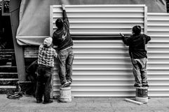 Grayscale Photo of Three Men Arranging Metal Wall royalty free stock photos