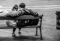 Grayscale Photo of Two Person Sitting on a Bench stock photo