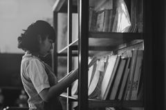 Grayscale Photo of a Woman Holding a Book Inside the Library Stock Image