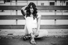 Grayscale Photo of Woman Sitting Near Fence royalty free stock image