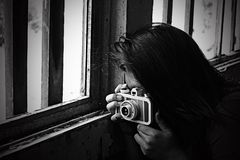 Grayscale Photo of Woman Taking Photo Beside Window stock image