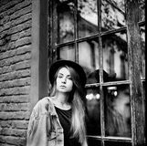 Grayscale Photo of Women's Denim Jacket and Hat Leaning on Window royalty free stock photography