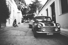 Grayscale Photography of a Black and White Car in a Road Near 3 Person Sitting Near a Green Tree Stock Image