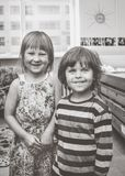 Grayscale Photography of Boy and Girl Standing Near Wooden Bed Inside Room stock photo