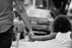 Grayscale Photography of Father and Daughter Holding Each Other While Walking stock photography