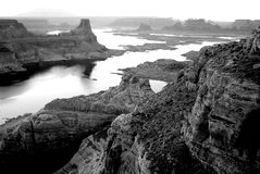Grayscale Photography of High Rise Rock Near Body of Water Stock Photo