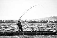 Grayscale Photography of Man Holding a Fishing Rod Near Body of Water Stock Image