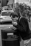 Grayscale Photography of Man Leaning on Black Trash Bin royalty free stock images
