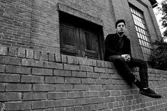 Grayscale Photography of Man Sitting on Brick Fence Royalty Free Stock Photo