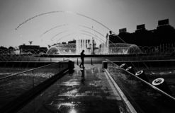 Grayscale Photography of Man Standing Near Fountain royalty free stock images
