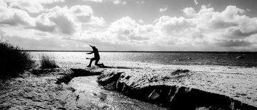 Grayscale Photography of a Person Jumping over Body of Water Stock Photography