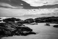 Grayscale Photography of Rocks on Seashore during Daytime Stock Photo