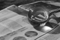 Grayscale Photography of Round Clear Paper Weight on Newspaper stock photography