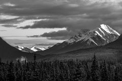 Grayscale Photography Of Snow Covered Mountain Under Cloudy Sky stock photography
