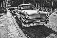 Grayscale Photography of Vintage Car Beside Pavement Stock Photo