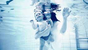Grayscale Photography of Woman Holding Baby in Swimming Pool royalty free stock image