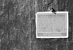 Grayscale rusty grungy old sign on a cement wall Stock Photo