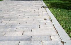 Graystone-Bürgersteig mit Gras Hintergrund, Natur Stockfotos