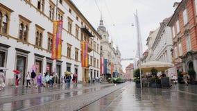 Graz, Áustria, em junho de 2017: Rua de Herrengasse em Graz Tempo chuvoso, pedestres com guarda-chuvas Lugar popular entre video estoque