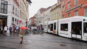Graz Österrike, Juni 2017: Regnigt väder på den berömda Herrengasse gatan i staden av Graz i Österrike Intensiv trafik lager videofilmer