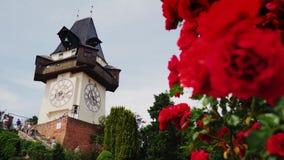 Graz, Austria, giugno 2017: Vecchia torre di orologio con i fiori rosa nella priorità alta Vicino passeggiata dei turisti Uno del stock footage