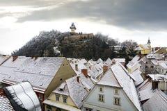 Graz-Winterszene mit Glockenturm und schneebedeckten Dachspitzen Stockfotos